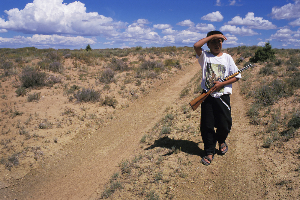 Herding - Darren Shorty looks for his family's sheep herd near Big Mountain in northern Arizona.  Shorty carries the rifle to protect the sheep from coyotes and to shoot small game for the family's dinner table.