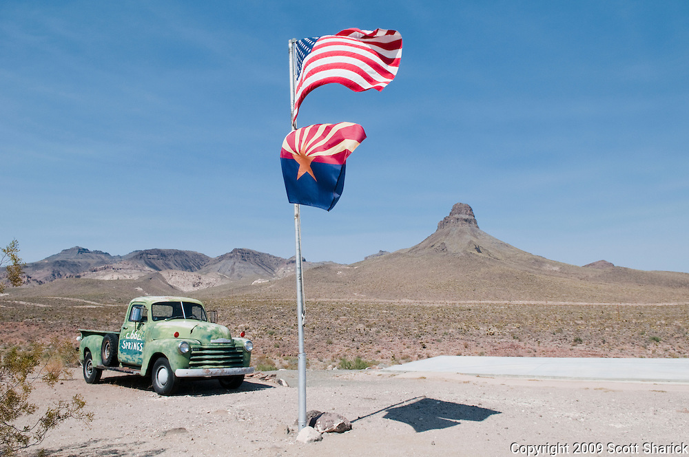 Arizona and American flags blowing in the wind near an old green truck in the Arizona desert. Missoula Photographer