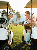 Young golfers sitting in golf cart holding score card