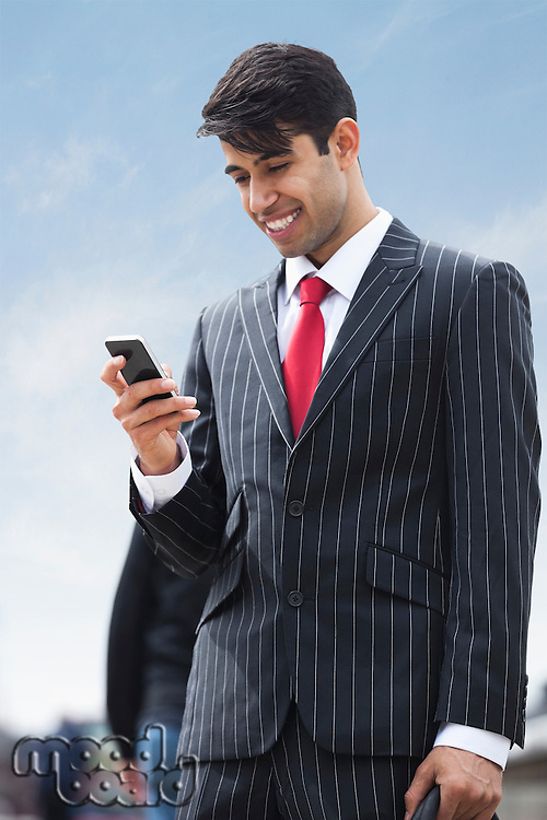 Happy Indian businessman using cell phone