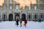 Three women with shopping bags outside The Royal Palace, Stockholm, Sweden in winter.