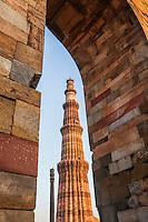 Iron pillar of Delhi seen with Qutub Minar through a brick archway, Qitb complex, Delhi, India.