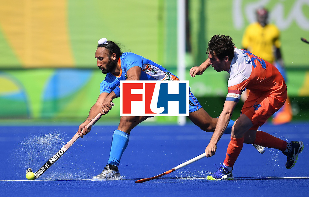 India's Sardar Singh (L) hits the ball as Netherland's Robert van der Horst tries to stop him during the men's field hockey Netherland's vs India match of the Rio 2016 Olympics Games at the Olympic Hockey Centre in Rio de Janeiro on August, 11 2016. / AFP / MANAN VATSYAYANA        (Photo credit should read MANAN VATSYAYANA/AFP/Getty Images)