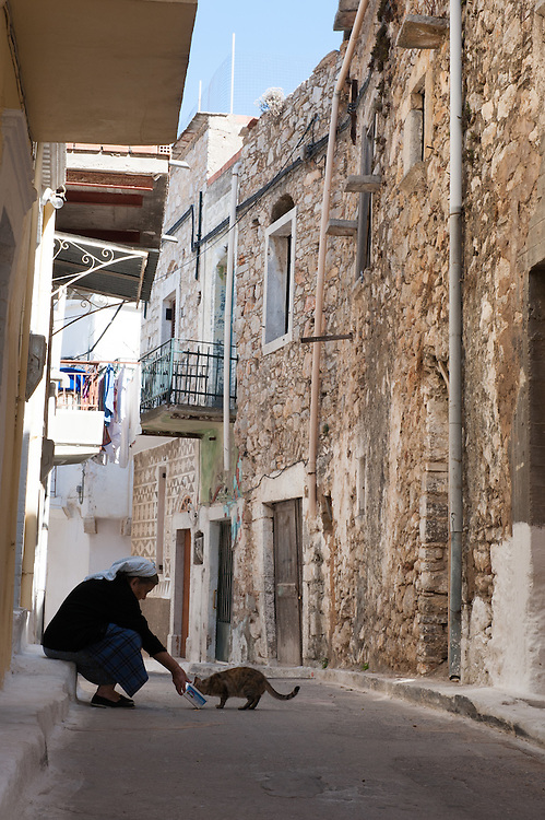 An old woman feeding a cat in an alley in the medieval village of Pyrgi, Chios, Greece.<br /> <br /> Pyrgi in Chios is known as the &quot;painted village&quot; on account of the decoration of the houses. The village still keeps its medieval style and together with the other Mastichochoria (Mastic Villages) are in the list of the Intangible Cultural Heritage of Humanity of UNESCO