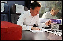 """File Photo - Prime Minister David Cameron leaves official red box behind on train.<br /> The Prime Minister David Cameron working on the train to Cardiff, Tuesday July 26, 2011. Photo By Andrew Parsons / i-Images.<br /> The Prime Minister who was going to a wedding near York got the 7.44am train at King's Cross on Saturday 7th September 2013, The PM departed the train, leaving the red box behind with the key still in it and no security within touching distance. A No10 spokesman said last night: 'The box was not left unattended. """"The Prime Minister's security detail was there at all times.""""<br /> Monday 9th September, 2013. Photo By Andrew Parsons / i-Images."""