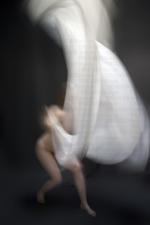 A naked young woman moving with  a white veil