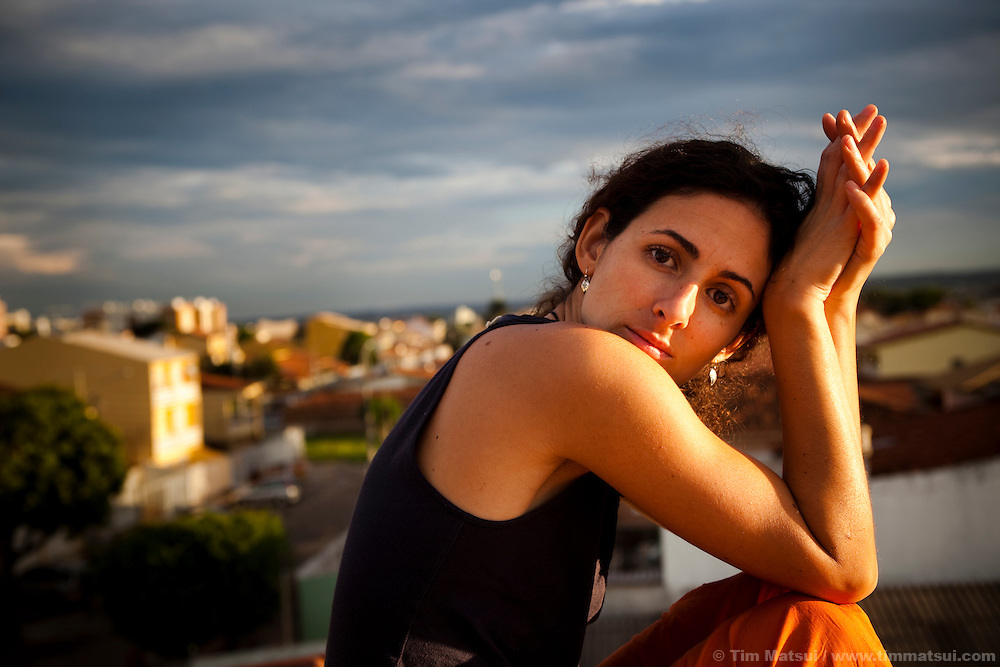 A young Brazilian woman sits on a rooftop at sunset in Brasilia, Brazil.