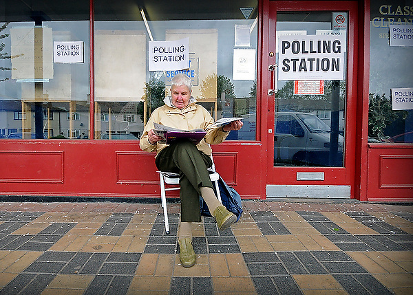 A polling station warden reads the local paper outside a Launderette used as a polling station in Hedington Oxford