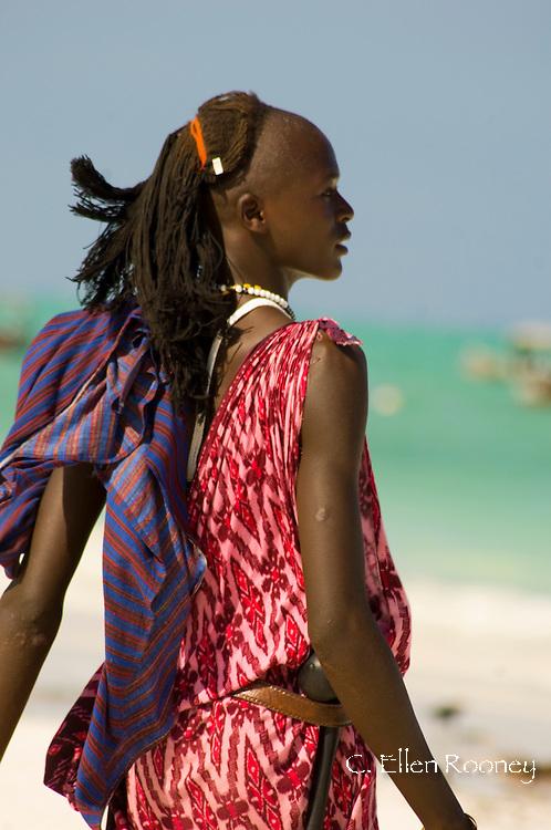 A Massai tribesman on Paje Beach wearing colourful native dress.  Paje, Zanzibar, Tanzania