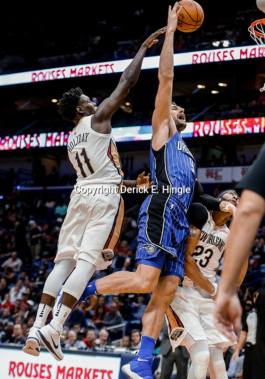 Oct 30, 2017; New Orleans, LA, USA; Orlando Magic center Nikola Vucevic (9) is fouled by New Orleans Pelicans guard Jrue Holiday (11) on a dunk attempt during the second quarter of a game at the Smoothie King Center. Mandatory Credit: Derick E. Hingle-USA TODAY Sports