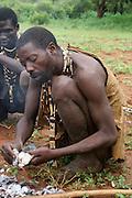 Africa, Tanzania, Lake Eyasi, Hadza man cooking a hunted bird on a campfire Small tribe of hunter gatherers AKA Hadzabe Tribe April 2006