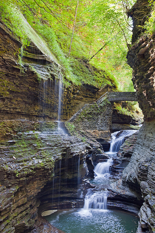 Watkins Glen State Park, New York State.<br /> From Wikipedia:  &quot;Watkins Glen State Park is located outside the village of Watkins Glen, New York, south of Seneca Lake in Schuyler County in the Finger Lakes region. The park's lower part is near the village, while the upper part is open woodland. It was opened to the public in 1863 and was privately run as a tourist resort until 1906, when it was purchased by New York State. Since 1924, it has been managed by the Finger Lakes Region of the New York State Office of Parks, Recreation and Historic Preservation.<br /> &quot;Jacob's Ladder, near the upper entrance to the park, has 180 stone steps, part of the over 800 total on the trails. The centerpiece of the park is a 400-foot-deep (120 m) narrow gorge cut through rock by a stream &ndash; Glen Creek &ndash; that was left hanging when glaciers of the Ice age deepened the Seneca valley, increasing the tributary stream gradient to create rapids and waterfalls wherever there were layers of hard rock. The rocks of the area are sedimentary of Devonian age that are part of a dissected plateau that was uplifted with little faulting or distortion. They consist mostly of soft shales, with some layers of harder sandstone and limestone.<br /> &quot;The park features three trails &ndash; open mid-May to early November &ndash; by which one can climb or descend the gorge. The Southern Rim and Indian Trails run along the wooded rim of the gorge, while the Gorge Trail is closest to the stream and runs over, under and along the park's 19 waterfalls by way of stone bridges and more than 800 stone steps. The trails connect to the Finger Lakes Trail, an 800-mile (1280 km) system of trails throughout New York state.