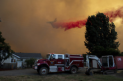 July 31, 2018 - Clearlake, California, U.S. - Retardant is dropped by a DC-10 ahead of the fire on Hendricks Road on Tuesday, July 31, 2018 in Clearlake. Mendocino Complex fires had burned 90,212 acres by Wednesday morning, Cal Fire said. (Credit Image: © Jose Luis Villegas/Sacramento Bee via ZUMA Wire)