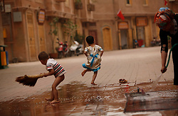 A picture made available on 31 May 2013 of children of the Uighur  ethnic group playing while cleaning outside their home in the old town of Kashgar, western edge of China's Xinjiang Uighur Autonomous Region, China 24 May 2013. Uighurs, a Muslim ethnic minority group in China, make up about 40 per cent of the 21.8 million people in Xinjiang, a vast, ethnically divided region that borders Pakistan, Afghanistan, Kazakhstan, Kyrgyzstan and Mongolia. Other ethnic minorities living in here include the Han Chinese, Kyrgyz, Mongolian and Tajiks people. In the restive region of Kashgar, western end of Xinjiang where the North and South Silk road meets, Uighurs comprise of more than 90 per cent of the 3.9 million population. Most practice a moderate form of Islam and religion is a major part of most ordinary Uighurs' lives. Tensions have been high between the Uighurs and the dominant Han Chinese as Uighurs complain of cultural and religious repression and claim that Han Chinese migrants enjoy the main benefits of development in the oil-rich but economically backward region.