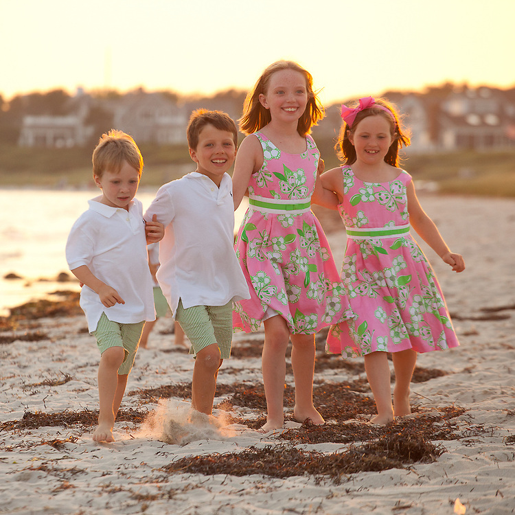Photo of four siblings running along the beach in Harwich at Bank Street Beach on Cape Cod