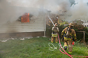 Firefighters battle a blaze with a firehose and use it to spary water on a burning house.