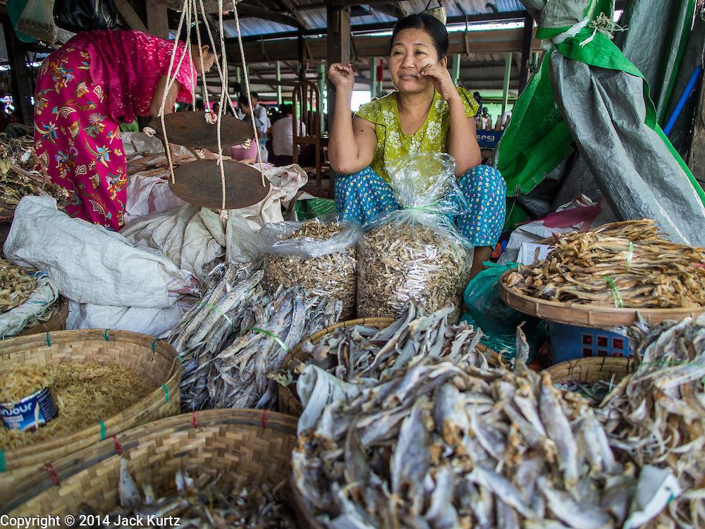 08 NOVEMBER 2014 - SITTWE, RAKHINE, MYANMAR:  A woman sells dried fish in the market in Sittwe. Sittwe is a small town in the Myanmar state of Rakhine, on the Bay of Bengal.  PHOTO BY JACK KURTZ