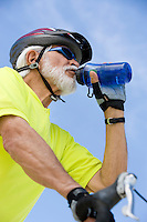 Senior man cycling and drinking water