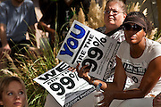 "22 OCTOBER 2011 - PHOENIX, AZ:    An Occupy Phoenix protester fans herself with her placard during the General Assembly meeting of protesters in Phoenix Saturday. The high in Phoenix Saturday was an unseasonably high of 95. The demonstrations at Occupy Phoenix, AZ, entered their second week Saturday. About 50 people are staying in Cesar Chavez Plaza, in the heart of downtown. The crowd grows in the evening and on weekends. Protesters have coordinated their actions with police and have gotten permission from the city to set up shade shelters and sleep in the park, but without tents or sleeping bags, which is considered ""urban camping,"" instead protesters are sleeping on the sidewalk.      PHOTO BY JACK KURTZ"