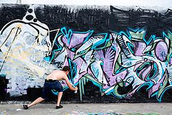 Graffiti artist at work on wall in bohemian Mauer Park in Prenzlauer Berg in Berlin Germany