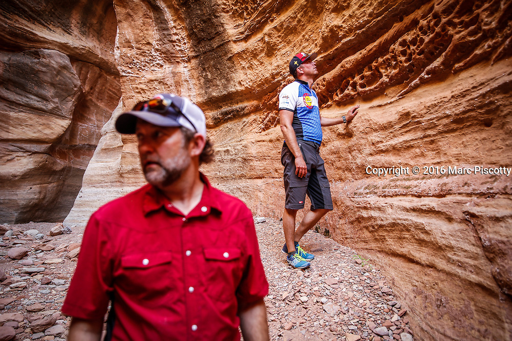 SHOT 10/15/16 1:03:18 PM - Doug Starkey (left) of Steamboat Springs, Co. and Mike Tryggestad of Denver, Co. explore a slot canyon along the White Rim Trail. The White Rim is a mountain biking trip in Canyonlands National Park just outside of Moab, Utah. The White Rim Road is a 71.2-mile-long unpaved four-wheel drive road that traverses the top of the White Rim Sandstone formation below the Island in the Sky mesa of Canyonlands National Park in southern Utah in the United States. The road was constructed in the 1950s by the Atomic Energy Commission to provide access for individual prospectors intent on mining uranium deposits for use in nuclear weapons production during the Cold War. Four-wheel drive vehicles and mountain bikes are the most common modes of transport though horseback riding and hiking are also permitted.<br /> (Photo by Marc Piscotty / &copy; 2016)