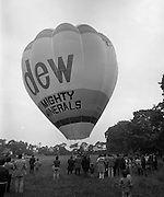 Dew Mighty Minerals Hot Air Balloon.   (H15)..1974..07.08.1974..08.07.1974..7th August 1974..The launching of the Dew Mighty Minerals hot air balloon,took place in Tullamore,Co Offaly last night,as part of the Tullamore Festival Week. The balloon was piloted by Mr Wilf Woollett,a veterinary surgeon from Loughrea,Co Galway and his co-pilot was Kevin Haugh. Miss Rosemary Mannion,the Offaly Rose of Tralee contestant sent the balloon on its way by popping a bottle of Champagne over it.  The balloon itself has a capacity of 56,000 cubic feet,is 60ft high and 50ft wide. It is made from nylon/polyproplene. The basket is 2ft square by 3ft high and carries two people,it is attached to the balloon by steel cables..Wilf Woollett has piloted the balloon in the U.S. and Britain and is a member of the Dublin Balloon Club...With the burner at full blast the balloon is up and ready for lift off.The support crew are pictured stabilising the balloon before release.