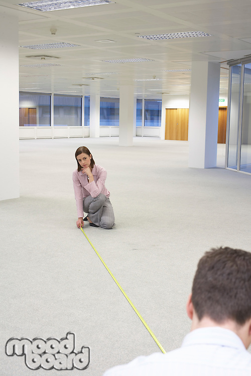 Man and Woman Measuring New Office Space