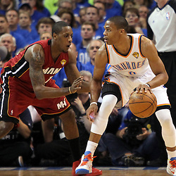 Jun 12, 2012; Oklahoma City, OK, USA;  Oklahoma City Thunder point guard Russell Westbrook (0) dribbles as he is defended by Miami Heat point guard Mario Chalmers (15) during the first quarter of game one in the 2012 NBA Finals at the Chesapeake Energy Arena.  Mandatory Credit: Derick E. Hingle-US PRESSWIRE
