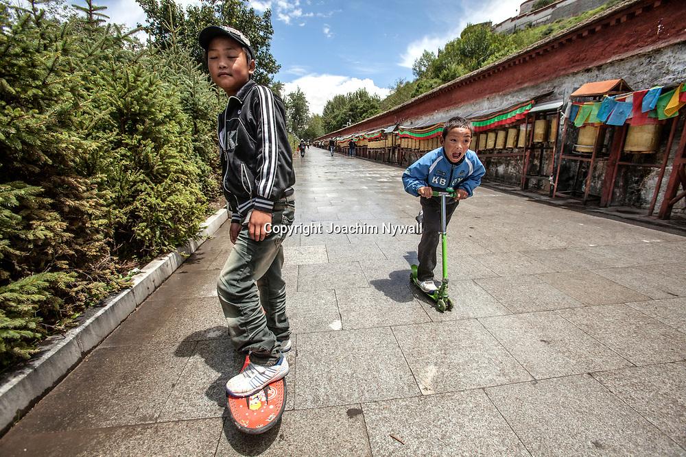 Lhasa 2011 Tibet<br /> Killar p&aring; kickbike och skateboard bredvid pilgrimsleden med b&ouml;nesnurror runt Potalapalatset i Lhasa<br /> <br /> ----<br /> FOTO : JOACHIM NYWALL KOD 0708840825_1<br /> COPYRIGHT JOACHIM NYWALL<br /> <br /> ***BETALBILD***<br /> Redovisas till <br /> NYWALL MEDIA AB<br /> Strandgatan 30<br /> 461 31 Trollh&auml;ttan<br /> Prislista enl BLF , om inget annat avtalas.