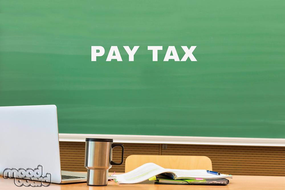 Pay Tax written on black board in classroom