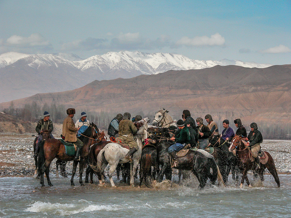 Image of Tajik horsemen fighting for control of the buz (a stuffed goat) in a river at a buzkashi event in the village of Kostarosh, northwest Tajikistan