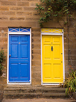 a yellow and a blue door on 2 terraced houses