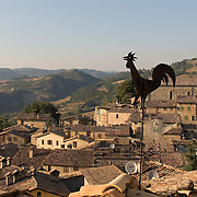 Black metal rooster weathervane above rooftop view of the Umbrian hilltown of Montone Italy