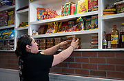 Anahi Rojas stocks the shelves of El Panzon Panaderia with Mexican speciality desserts and bakery items in Madison, Wisconsin, Thursday, June 20, 2019.