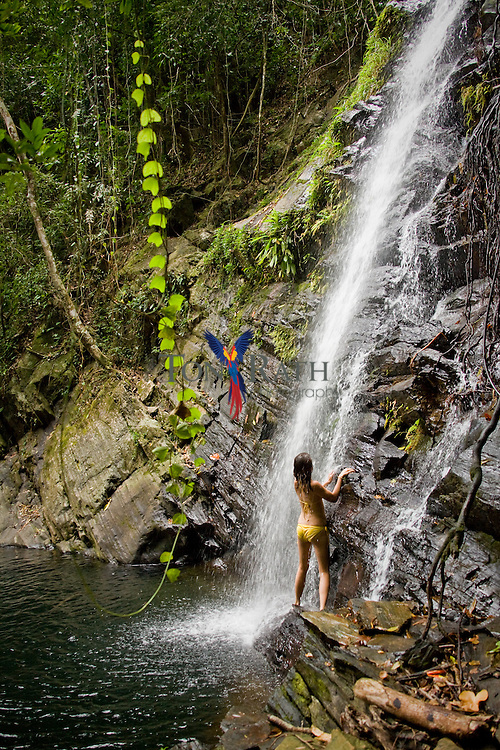 Young women at a secluded jungle waterfall in the Stann Creek District of Belize.