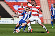Conor McAleny (24) of Wigan Athletic and Luke McCullough (4) of Doncaster Rovers during the Sky Bet League 1 match between Doncaster Rovers and Wigan Athletic at the Keepmoat Stadium, Doncaster, England on 16 April 2016. Photo by Ian Lyall.