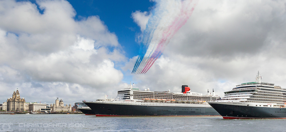 The Red Arrows in formation as Cunard&rsquo;s fleet gather together in spectacular fashion in Liverpool, its spiritual home, as the company marked its 175th anniversary. Left to right: Queen Elizabeth, Queen Mary 2, Queen Victoria. The historic lines' three ships, the largest passenger ships ever to muster together on the River Mersey, lined up just 130 metres apart.<br /> The vessels lined up three abreast at Liverpool's Pier Head beside its iconic Three Graces: The Royal Liver Building, The Cunard Building and The Port of Liverpool Building. <br /> Picture date Monday 25th May, 2015.<br /> Picture by Christopher Ison. Contact +447544 044177 chris@christopherison.com