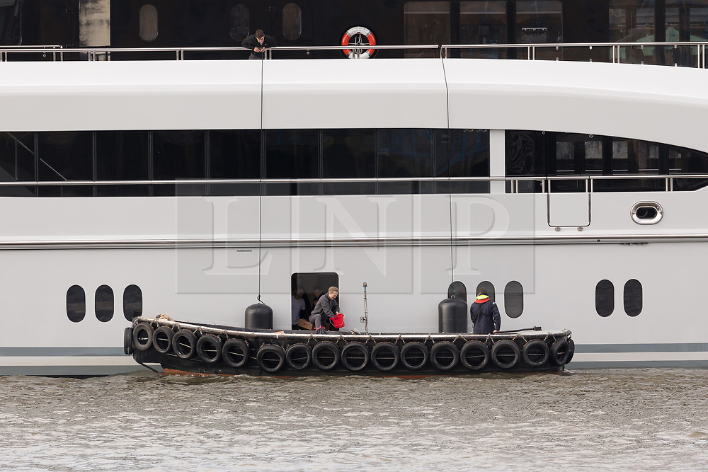 © Licensed to London News Pictures. 29/03/2018. London, UK. People working with a support boat to the 220ft custom luxury superyacht, 'Global' moored at Butlers Wharf near Tower Bridge during a London visit. Previously named, Kismet during her last central London visit, she underwent a refit which saw her moved up 51 places in Boat International's list of top 200 largest super yachts in the world, boasting numerous luxuries such as a helipad, cinema and jacuzzi. Believed to be owned by Fulham Football Club chairman, Shahid Khan, Global can be chartered for an estimated £1m per week. Powered by 2 Caterpillar (3512 B) 2,038hp diesel engines and propelled by her twin screws propellers, Global is capable of a top speed of 15.5 knots, and comfortably cruises at 14 knots. . Photo credit: Vickie Flores/LNP