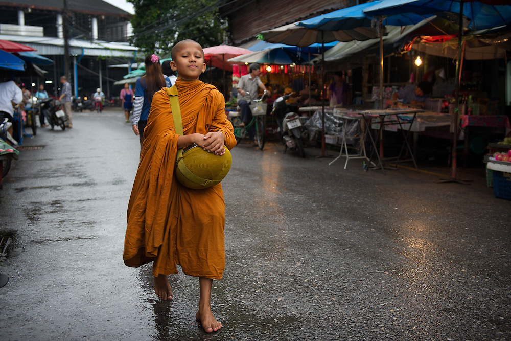 A young monk gathering morning alms in the market at Nakhon Nayok, Thailand PHOTO BY LEE CRAKER