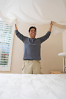 Mid-adult man making a bed