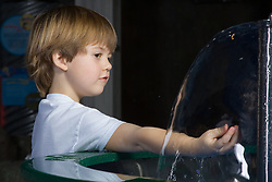 United States, Washington, Bellevue, KidsQuest Children's Museum, boy exploring water at Waterways exhibit
