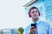Portrait of smiling mature businessman listening to music on his smartphone with headphones on