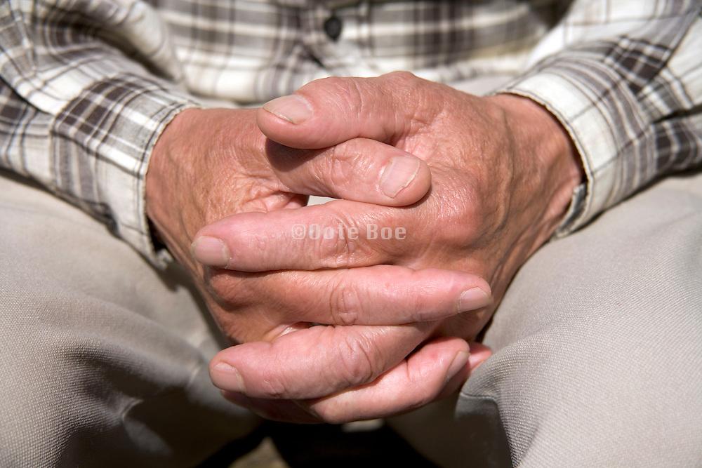 folded hands of an elderly man