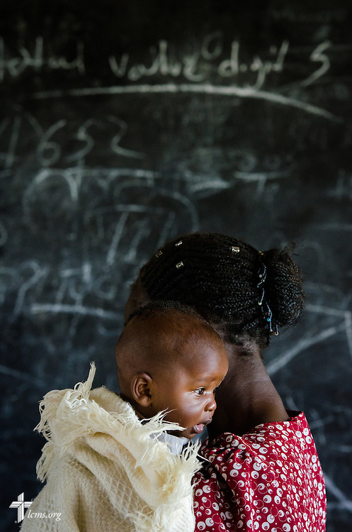 A woman and her infant wait for treatment during the Mercy Medical Team clinic Thursday, June 12, 2014, at the Luanda Doho Primary School in Kakmega County, Kenya. LCMS Communications/Erik M. Lunsford
