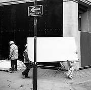 Obscured builders converting a Regent Street shop, carry an awkward hardboard panel on city pavement.