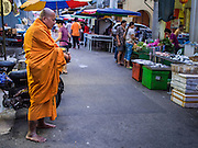 07 OCTOBER 2014 - GEORGE TOWN, PENANG, MALAYSIA: A Theravada Buddhist monk solicits alms in a market in George Town (also Georgetown), the capital of the state of Penang in Malaysia. Named after Britain's King George III, George Town is located on the north-east corner of Penang Island. The inner city has a population of 720,202 and the metropolitan area known as George Town Conurbation which consists of Penang Island, Seberang Prai, Kulim and Sungai Petani has a combined population of 2,292,394, making it the second largest metropolitan area in Malaysia. The inner city of George Town is a UNESCO World Heritage Site and one of the most popular international tourist destinations in Malaysia.         PHOTO BY JACK KURTZ