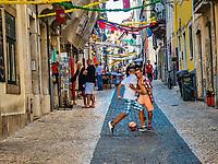 Enfants jouant dans le Bairro Alto lors de la fete des saint populaires.<br /> Fete des saints populaires à Lisbonne<br /> Du 12 au 29 juin, tout Lisbonne honore saint Antoine de Padoue, le saint patron de la ville, le 13 (ferie a Lisbonne) et saint Jean le 24. Apres le defile en fanfares, bals musettes et sardinhas grillees à volonté dans les quartiers populaires. Le tout emballé dans un carnaval de guirlandes de papier et de fanions. <br /> La municipalite de Lisbonne y a ajoute les festas de Lisboa, une avalanche d'expositions, de theatre de rue, de concerts... du meilleur cru international. <br /> Ces festivites se prolongent pendant tout l'ete et offrent de nombreux evenements – spectacles de fado, concerts de jazz et d'autres genres musicaux, fado dans les tramways sillonnant la ville...