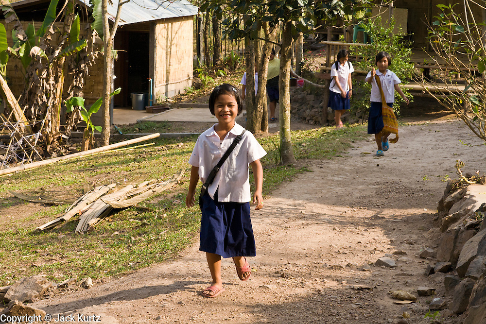 18 FEBRUARY 2008 -- BONG TI, KANCHANABURI, THAILAND: Burmese refugee children walk back the Bamboo School in Bong Ti, Thailand, about 40 miles from the provincial capital of Kanchanaburi. Sixty three children, most members of the Karen hilltribe, a persecuted ethnic minority in Burma, live at the school under the care of Catherine Riley-Bryan, whom the locals call MomoCat (Momo is the Karen hilltribe word for mother). She provides housing, food and medical care for the kids and helps them get enrolled in nearby Thai public schools. Her compound is about a half mile from the Thai-Burma border. She also helps nearby Karen refugee villages by digging water wells for them and providing medical care.  Photo by Jack Kurtz