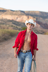 Hot All American cowboy with an open shirt standing on a dirt road