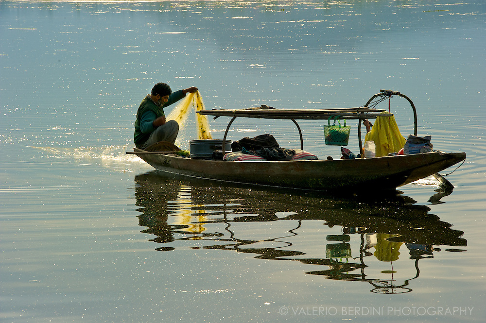 Husband and wife set the fishing nets at sunset in the open waters of Dal Lake. Kashmir. India